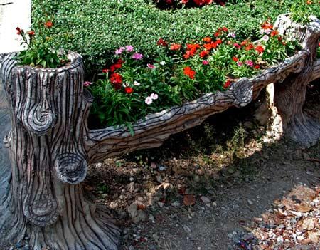 поделка из пня, исполненная в виде клумбы, в саду
