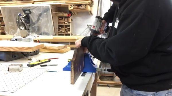 Доска зажата в кондукторе для точного насверливания отверстий