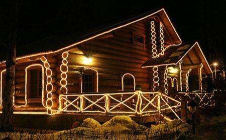 деревянный дом, украшенный светодиодными лентами